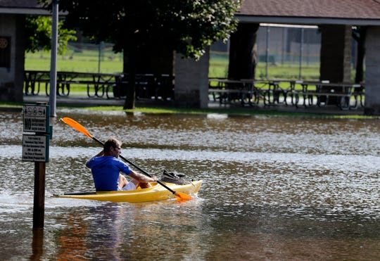 A man in a kayak checks out flooding on the river at Village Park in Thiensville.