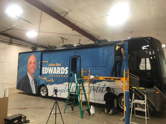 Workers put finishing touches on Gov. John Bel Edwards' campaign RV.