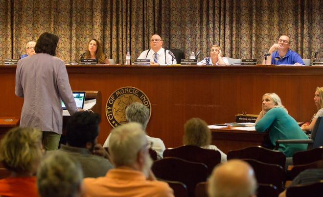 Council members watch a presentation from developers on a TV screen overhead about the proposed downtown apartments.