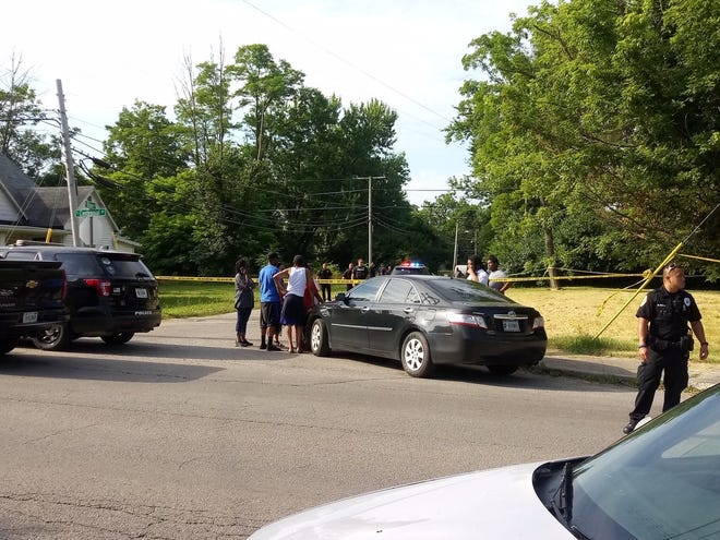 City police and citizens near the scene of the community's latest homicide, in the Whitely neighborhood on Tuesday morning.