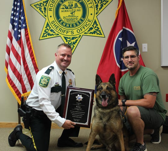 Sheriff Michael Van Dyke, K-9 Kane, and his handler, Det. Brett Keck, pose for a photo during Kane's recent retirement party.