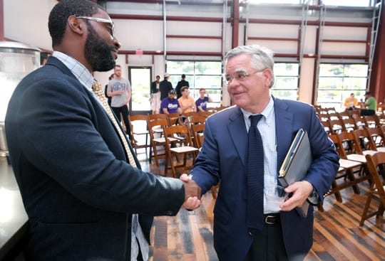 Metro councilman and mayoral candidate John Cooper, right, greets fellow mayoral candidate Nolan Starnes before The Nations Neighborhood Association's mayoral candidate Q&A at Fat Bottom Brewing in Nashville on July 1, 2019.
