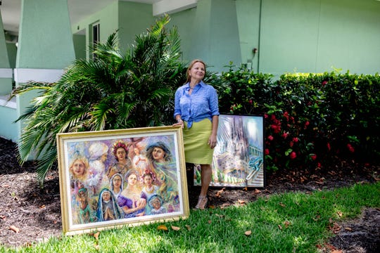 Olena Skiba stands with her artwork at the Naples Art Association in Naples on May 30, 2019.  Skiba, from Ukraine, has made a home for herself in Naples and works as an artist.