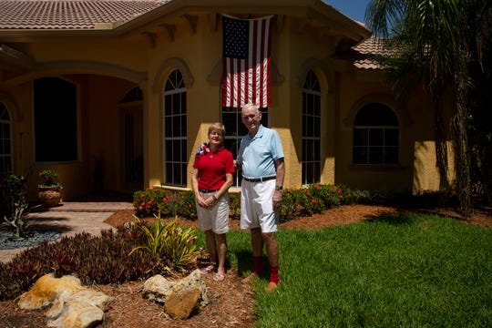 Elysee Marshall and Thomas J. Marshall pose for a portrait, Tuesday, July 2, 2019, at their home in East Naples. The United State flag that once flew over the United States Capital Building on July 4, 1976, is pictured behind the couple.