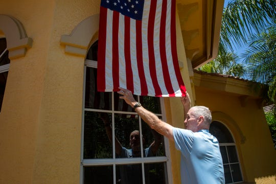 Thomas J. Marshall adjusts the U.S. Flag, Tuesday, July 2, 2019, hanging outside his home in East Naples. The flag once flew over the United States Capital Building on July 4, 1976.