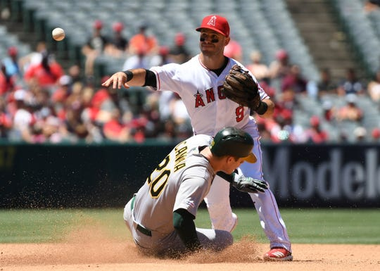 June 30, 2019; Anaheim, CA, USA; Los Angeles Angels second baseman Tommy La Stella (9) throws to first for the double play as Oakland Athletics designated hitter Mark Canha (20) is out at second during the fourth inning at Angel Stadium of Anaheim.