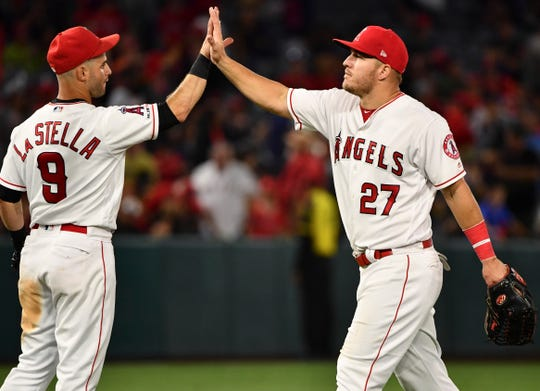 Jun 27, 2019; Anaheim, CA, USA; Los Angeles Angels center fielder Mike Trout (27) receives a high-fine from third baseman  Tommy La Stella (9) after defeating the Oakland Athletics at Angel Stadium of Anaheim.