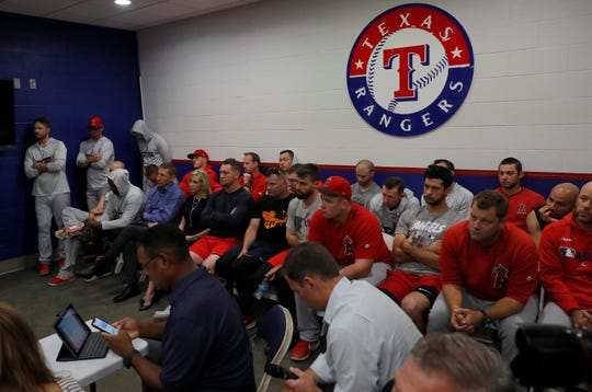 Los Angeles Angels players and staff listen as a news conference is underway regarding the death of Tyler Skaggs before a baseball game against the Texas Rangers in Arlington, Texas, Tuesday, July 2, 2019.