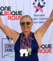Senior Games swimmer Yenny van Dinter raises her arms in victory after capturing three gold medals during national competition in Albuquerque.