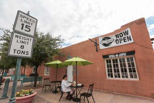 A woman sits outside of Main Street Vintage Mercado on Tuesday, July 2, 2019 after the shop opened the previous Saturday on Main Street and Las Cruces Avenue in Downtown Las Cruces.
