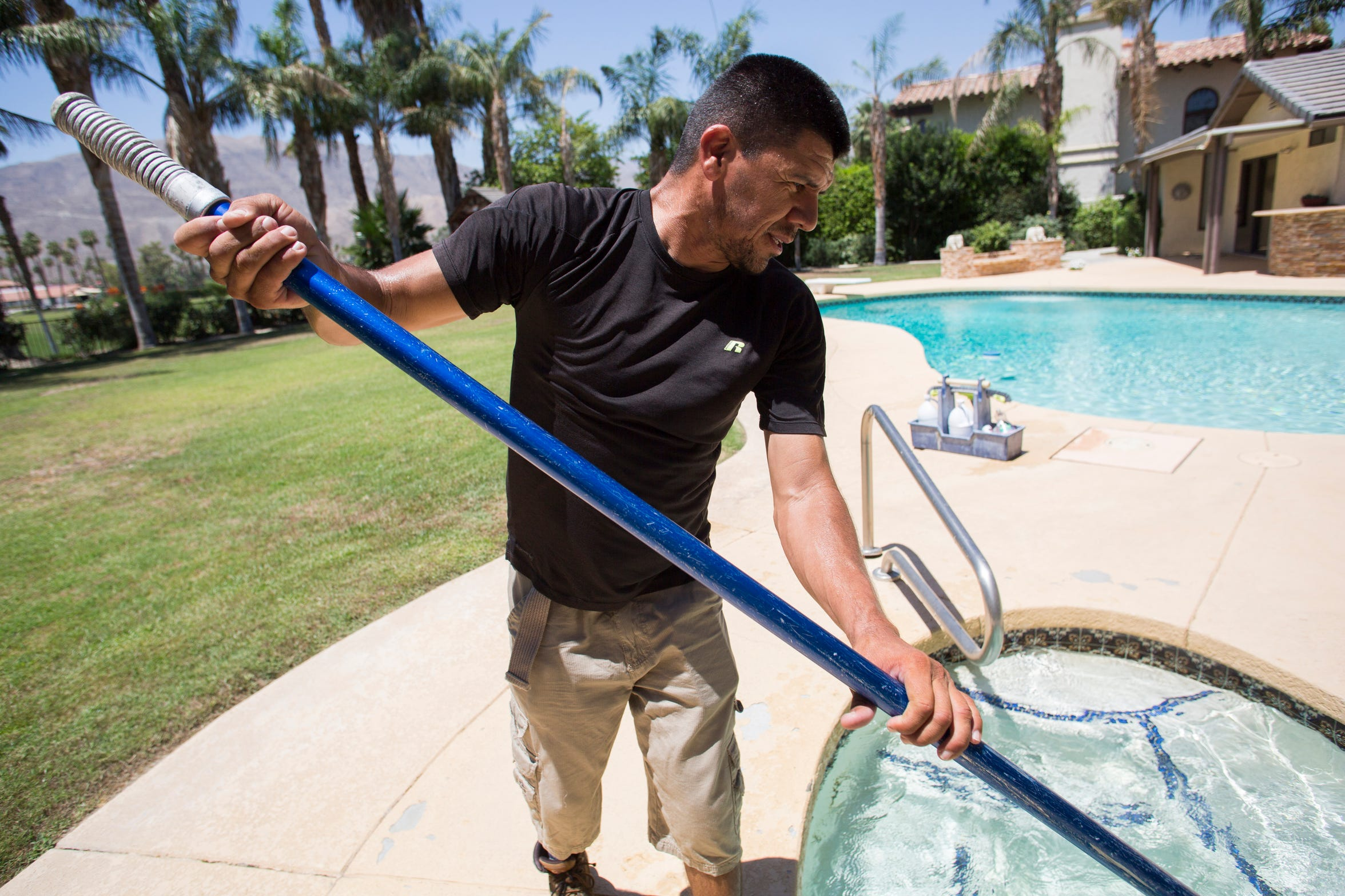 Miguel Vazquez cleans a pool in the Coachella Valley on June 19, 2019.