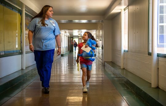 First grader Stephanie Rojas, 7, walks back to her class with dental coordinator Gizelle Jacobs after a dental visit at the Northwood Elementary School on Friday, May 31, 2019 in Sacramento. Twice a week a dental assistant and hygienist see student patients at an improvised clinic at the school in the Twin Rivers Unified School District.