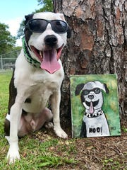 Koop'R, a certified search and rescue dog, poses next to his portrait painted by Micah Lapen. Together, Koop'R and Lapen embody Micah and the Moo, a Steps for Autism team.