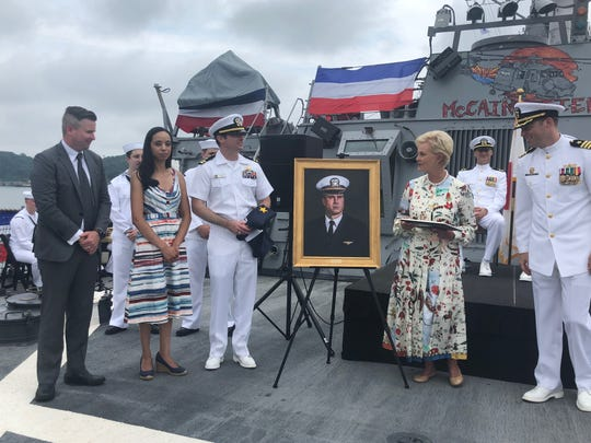 Cindy McCain, along with members of the McCain family, gather in Japan around a portrait of the late Sen. John McCain that will be added to the USS John S. McCain, along with portraits of his father and grandfather.