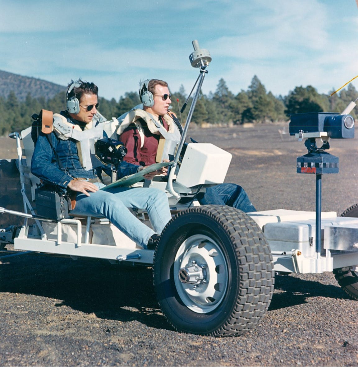 Astronauts James Irwin and David Scott drive the Grover vehicle at Cinder Lake Crater Field.