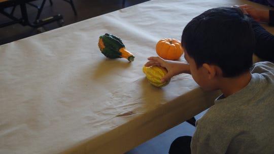 """Un niño inmigrante juega con unas calabazas durante un almuerzo colectivo en la Escuela Comunitaria """"Isabella Bird"""" en Denver, Colorado."""