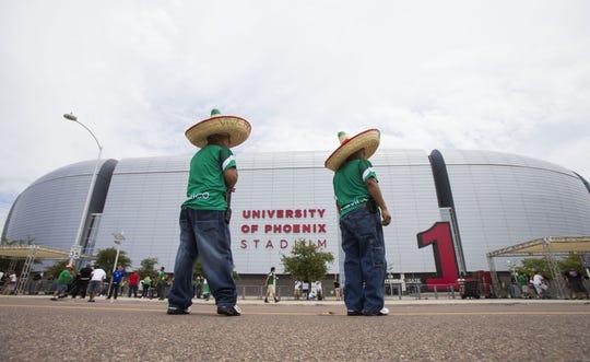 Dos aficionados mexicanos esperan para ingresar al estadio de Glendale.