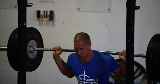 Eric Townsley squats during a a powerlifting workout at Black Powder CrossFit in Dallastown on Monday, July 1.