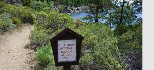 A sign near Creek Beach on the east shore of Lake Tahoe alerts visitors that the beach is clothing optional.