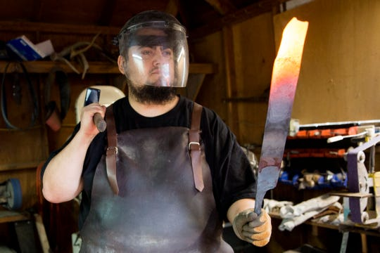 "Josh Navarrete, winner of History channel's ""Forged in Fire,"" demonstrates how he uses a forge to make knives at his home in Salem on July 2, 2019. Navarrete will spend about two days on each knife he makes."