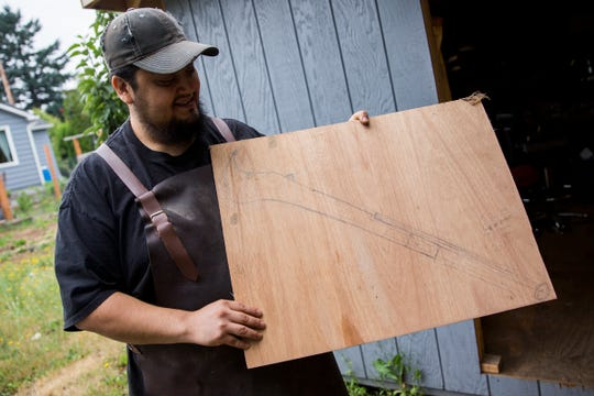 "Josh Navarrete, winner of History channel's ""Forged in Fire,"" holds a sketch of the Ram Dao sword he made in the final round of the show at his home in Salem on July 2, 2019."