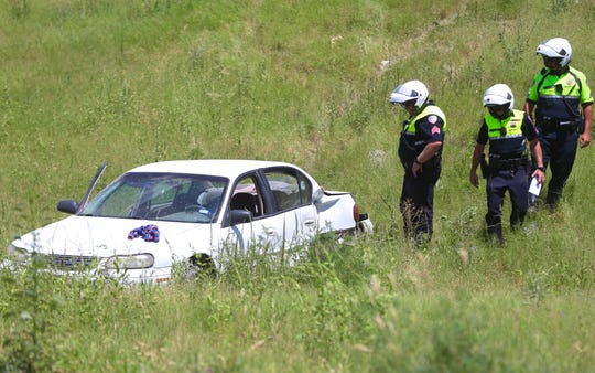 San Angelo police officers investigate the scene of a car crash near Loop 306 Tuesday afternoon.