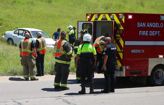 Emergency responders load the victim of a car crash into an ambulance Tuesday afternoon. The vehicle drove off Loop 306 in San Angelo after striking a guardrail.