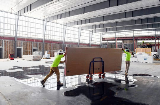 Construction workers move materials through the future volleyball courts at the Avera Human Performance Center on Louise Ave. on Tuesday, July 2, in Sioux Falls.