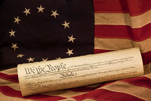 We the People, the opening words of the preamble to the Constitution of the USA, is prominent in this photograph of a rolled copy of the Constitution.