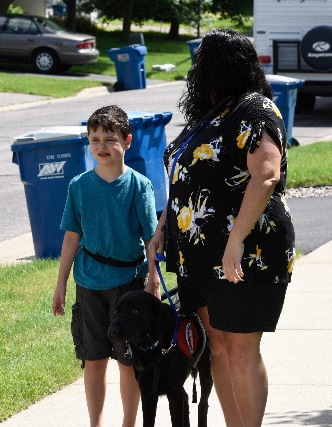 Carter Newville-Larson and his mom, Annie Newville, practice walking  Tuesday, July 2, 2019 with his service dog, Noah.