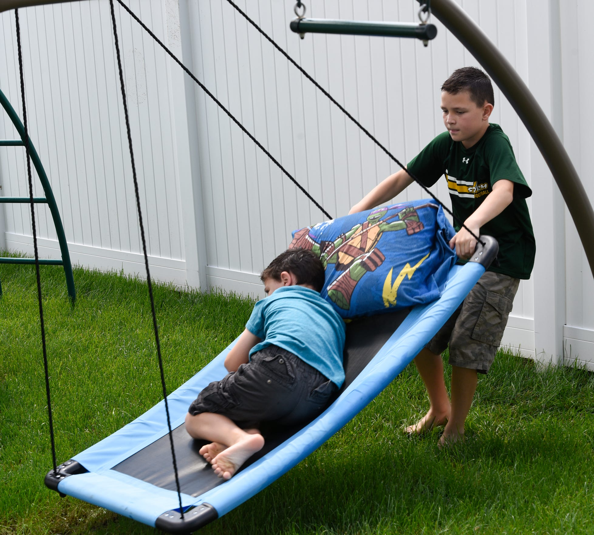 Tyson Newville-Larson pushes his brother Carter on a swing Tuesday, July 2, 2019.