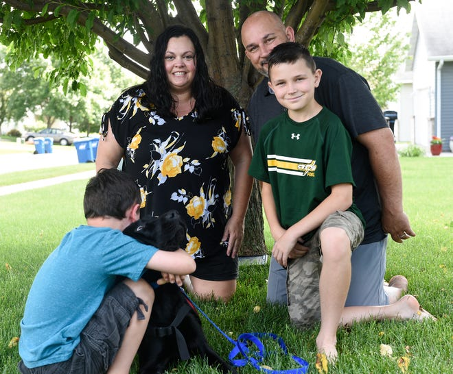 Carter Newville-Larson, 7, hugs his service dog, Noah, as his parents, Annie Newville and Jake Larson, along with his brother, Tyson Newville-Larson, 12, pose for a photo Tuesday, July 2, 2019.