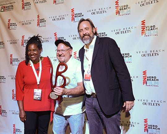 Director Mark Schimmel, center, receives the Jury Award for Documentary Short film from Dr. Stacie Walton, left, and Vero Beach Mayor Val Zudans.