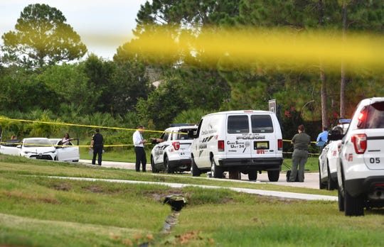 Port St. Lucie police vehicles park outside the home where an officer involved shooting happened earlier Monday,  as neighbors look over the scene blocked off with tape,  on the 3200 block of SW Constellation Rd.