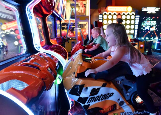 Children ride on a motorcycle arcade game at Sparetime Entertainment in Greenville.