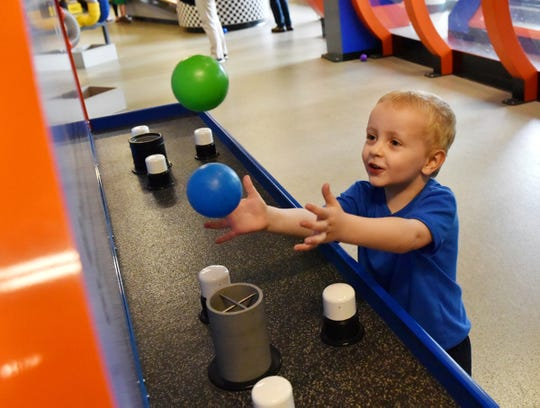 Emmett Cromer, 3, plays with plastic toy balls while they're suspended in a stream of air at the Children's Museum of the Upstate in Greenville.
