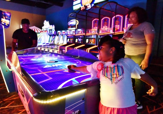 A family plays air hockey at Sparetime Entertainment in Greenville.