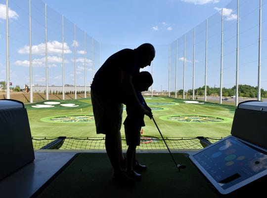 Ashan Hendi helps his son Ali hit a golf ball at Topgolf Greenville.
