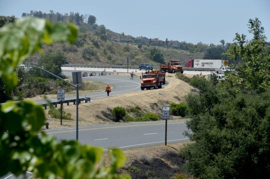 Caltrans workers cut back dried brush along Highway 23 in Moorpark on Tuesday near Los Angeles Avenue.