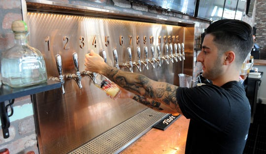 Harrison Bell, a bartender at Finney's Crafthouse & Kitchen in Ventura, pours one of the 30 selections on tap. The restaurant opened in June on the ground floor of the landmark Erle Stanley Gardner Building.
