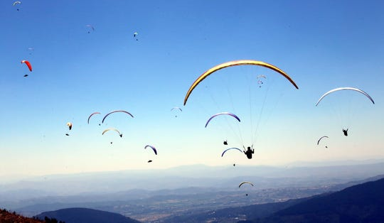 Paragliders soar during the 2019 Paragliding World Cup at the Serra da Estrela, the highest mountain range in continental Portugal, Manteigas July 2, 2019.