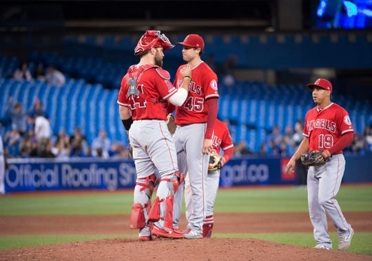 Angels catcher Kevan Smith talks with Tyler Skaggs during a June game.