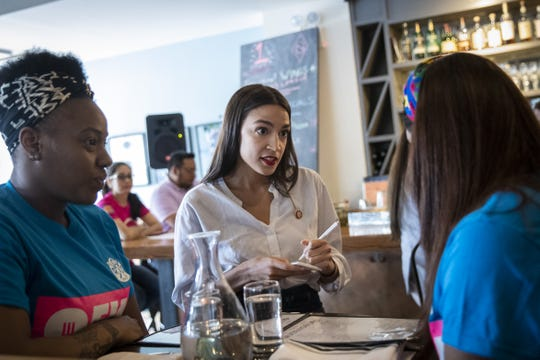 U.S. Rep. Alexandria Ocasio-Cortez, D-N.Y., waits on a table at the Queensboro Restaurant, May 31, 2019 in the Queens borough of New York City. Ocasio-Cortez participated in an event to raise awareness for the One Fair Wage campaign, which calls to raise the minimum wage for tipped workers to a full minimum wage at the federal level.