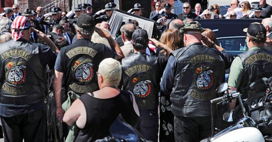 Members of the Jarheads Motorcycle Club and a police honor guard salute as the casket of Michael Ferazzi arrives at St. Peter's Catholic Church in Plymouth, Mass., Friday, June 28, 2019. Ferazzi, a motorcyclist and retired police officer, was killed in a fiery crash that claimed the lives of seven people riding with the Jarheads Motorcycle Club in New Hampshire. (AP Photo/Charles Krupa) ORG XMIT: MACK103