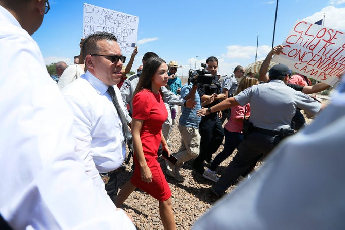 U.S. Rep. Alexandria Ocasio-Cortez, D-N.Y., is escorted back to her vehicle after speaking at the Border Patrol station in Clint, Texas about what she saw at the area border patrol facilities on July 1, 2019
