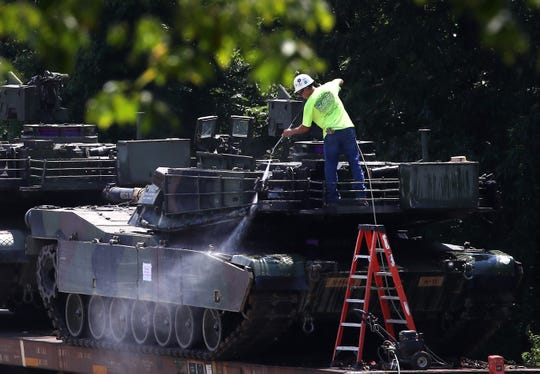 A worker washes one of two M1A1 Abrams tanks that are loaded on rail cars at a rail yard on July 2, 2019 in Washington, DC. President Trump asked the Pentagon for military hardware, including tanks, to be displayed during Thursdays July 4th Salute to America celebration at the Lincoln Memorial.