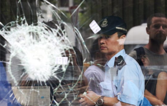 Police patrol after protesters broke glass panels at the Legislative Council building July 1.