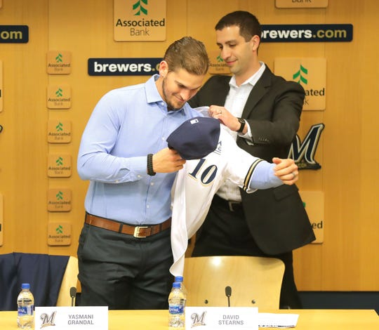 Milwaukee Brewers general manager David Stearns helps Yasmani Grandal don his No. 10 Brewers jersey at a news conference after he signed with the Brewers.