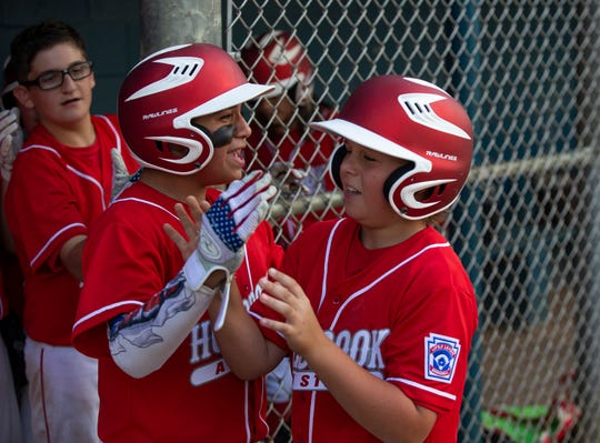 Holbrook's Max Rakestraw gets congratulated after scoring his team's first run of game. Holbrook plays Brick in a District 18 Little League game in Brick on July 2, 2019