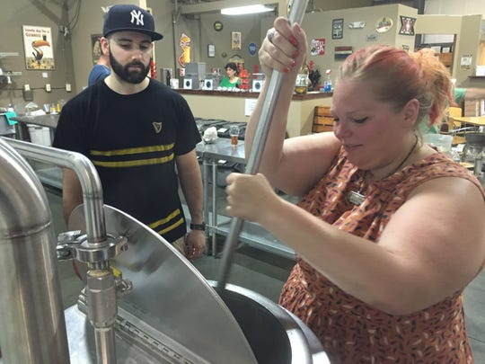 Brewmaster Lou Luzzo instructs Jen Meyer as she stirs an IPA at The Brewer's Apprentice in Freehold Township.